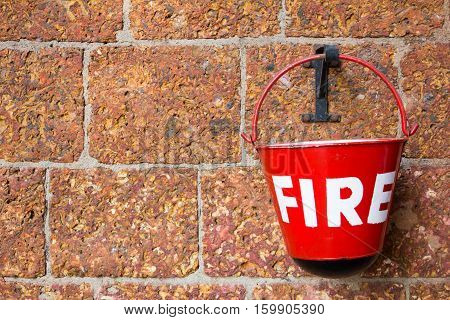 Red fire bin contain the sand on brick wall background