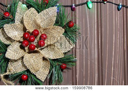 A Christmas background with a burlap decoration with berries on wooden bakground with Chritmas lights and copy space