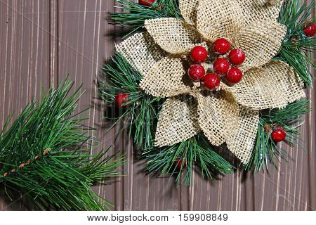 A Christmas background with a burlap decoration with berries on wooden bakground