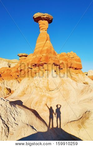 Traveling Couple Making Funny Picture Under Hoodoo Rock Formation In Arizona, Usa
