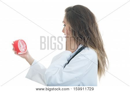 Serious female doctor holding clock and look serious.