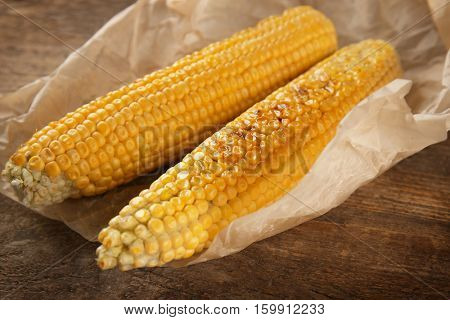 Tasty grilled corncobs on wooden table, close up view