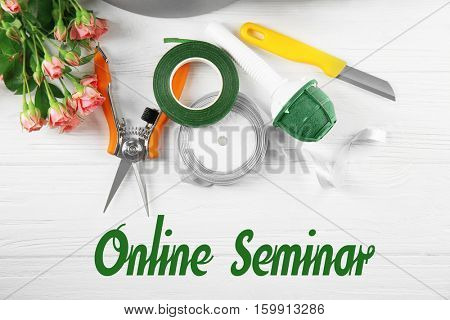 Text ONLINE SEMINAR with florist equipment on white wooden background. Florist and floral design tutorial concept.