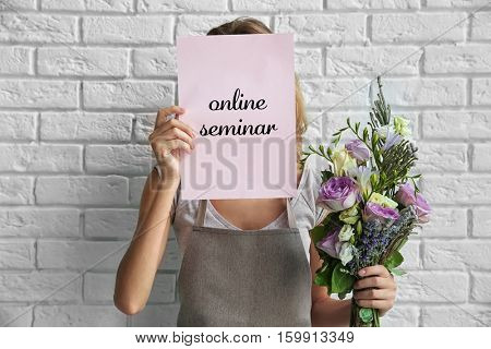 Woman holding paper with text ONLINE SEMINAR and bouquet on brick wall background. Florist and floral design tutorial concept.