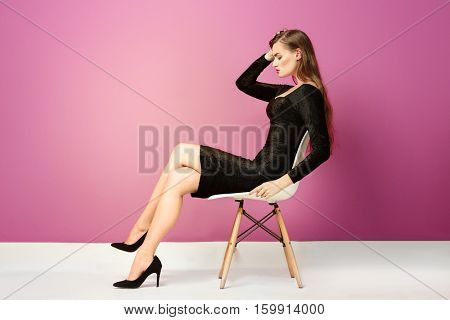 Gorgeous young woman in black evening gown posing on pink background