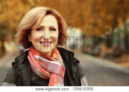 Closeup portrait of gorgeous middle aged woman on blurred background