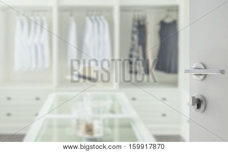 Opened White Door To Walk In Closet Room With White Hat And Jewelry Set On A Dresser Table