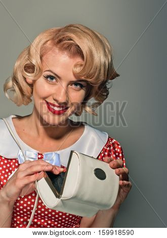 young beautiful caucasian woman posing with purse, over dirty yellow background, retro styling, pin up