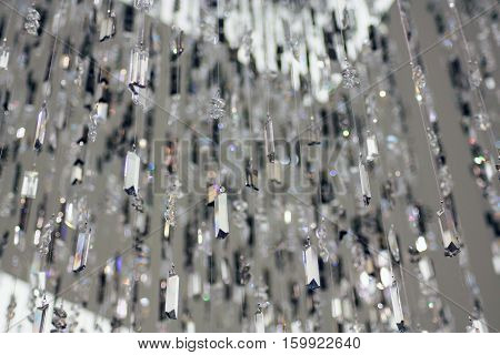 Strings of glass and metal beads hanging from a ceiling.