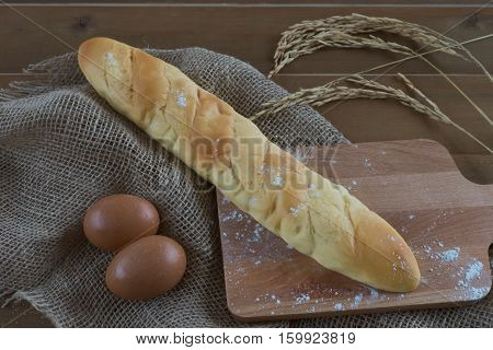 loaf piece of bread on wooden breadboard on wooden table and ear of rice golden color in morning sunrise / bread on breadboard