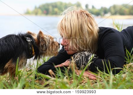 Woman and small dog portrait on lake shore background. Autumn lake nature tenderness