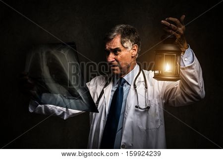 Doctor using a lantern to look at a radiography