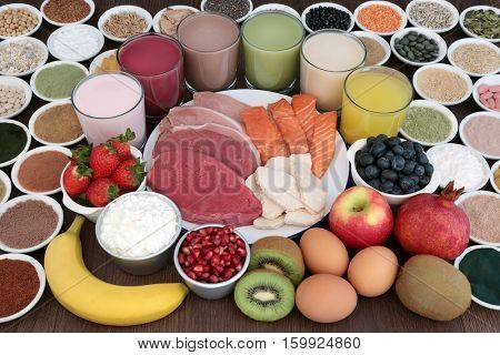 Body building  food and drinks with high protein lean meat and salmon, supplement powders, fruit, nuts, seeds, grains, cereals, pulses, herbs, dairy over oak background.