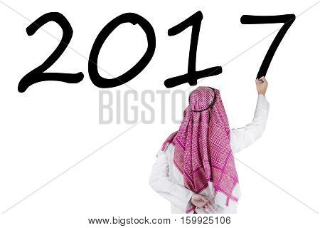 Back view of middle eastern male entrepreneur is writing numbers 2017 on the whiteboard