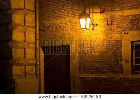 The old medieval brick wall of historical building with illuminated night lamp.
