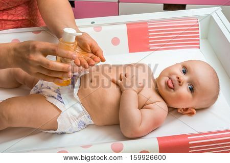 Mother Makes Massage For Her Baby And Apply Oil On The Hands