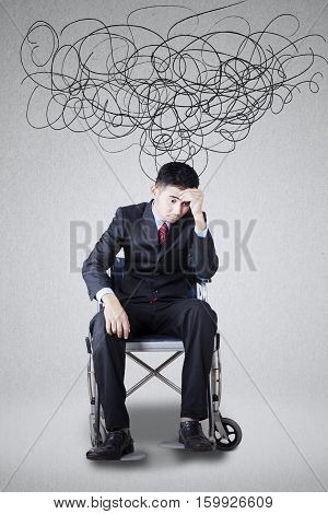 Image of a disabled young man wears formal suit and looks frustrated with scribbles above his head
