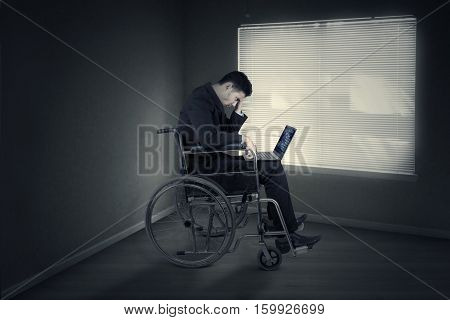 Picture of disabled businessman sitting on a wheelchair and expressing frustration while working with laptop