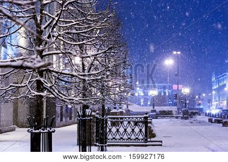 Snowflakes Fall Down On Night City, Covering Trees, Lampposts And Street By Snow