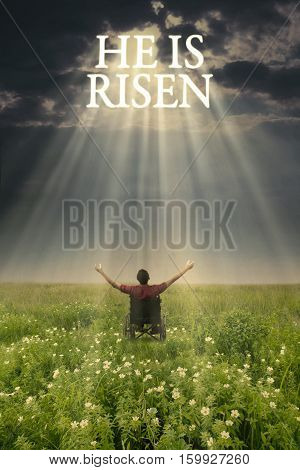 Back view of a young disabled male looking at text of he is risen on the sky while raising hands on the meadow