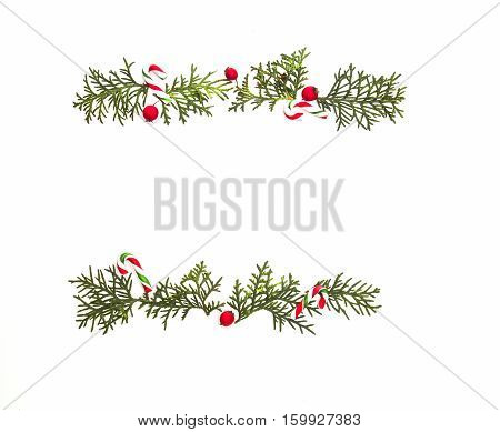 Christmas frame made of green thuja twigs and red wild rose fruits. Christmas composition on white background. Top view, flat lay. Winter holidays concept