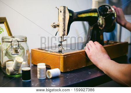 Hands Seamstress Work On The Sewing Machine. Young Blond Woman Working On A Mechanical Sewing Machin