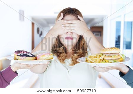 Portrait of fat woman closed eyes and reject junk food at home