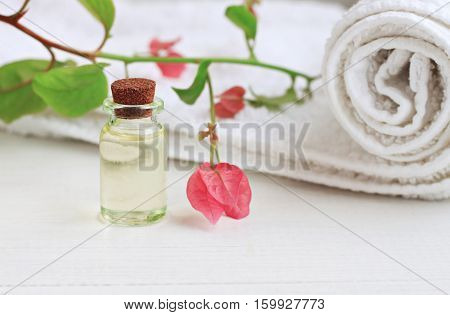 Essential oil glass bottle extract, delicate pink tropical flower, white towel. Botanical beauty and health care.