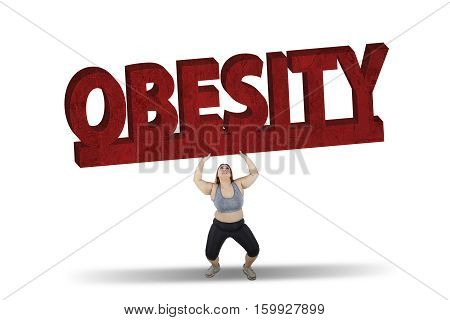 Picture of fat woman lifting a big obesity word while standing in studio isolated on white background