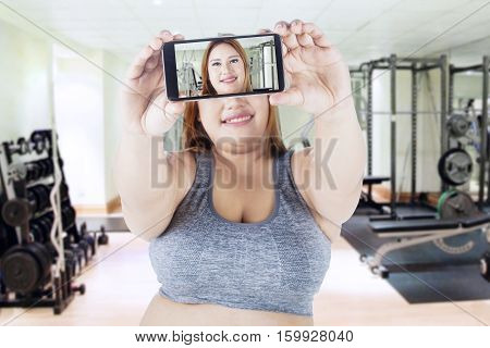 Portrait of fat woman taking selfie picture by using her smartphone while standing at the gym