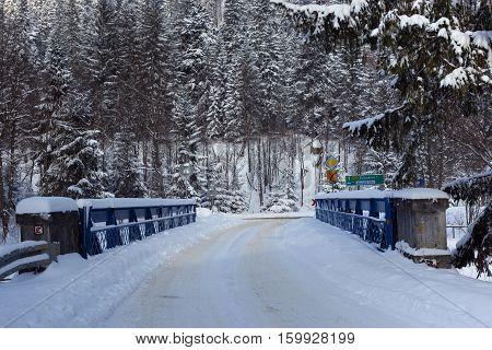Slovak-polish border bridge on the Lysa Polana in snowy forest in the High Tatras mountains. Border crossing on the road from Tatranska Lomnica (Slovakia) to Zakopane (Poland).