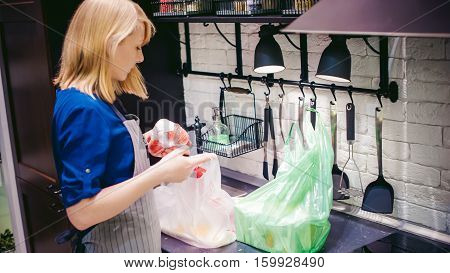 Woman With Shopping Bags Parses The Kitchen. Housewife In Apron In The Kitchen Arranges Bought Food