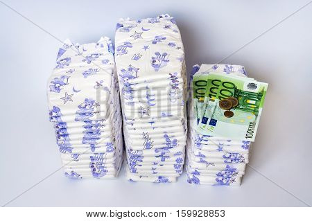 Pile of disposable diapers with euro money - expensive childcare