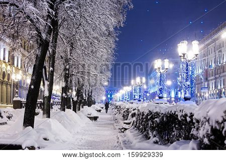 Winter City Street With Trees And Benches Covered In Snow And Lamp Posts With Christmas Lights