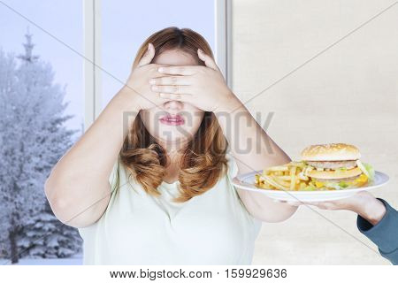 Portrait of obese woman closing her eyes and refusing junk food with winter background on the window