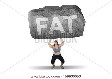 Obese woman lifting a big stone with fat word while standing in studio isolated on white background