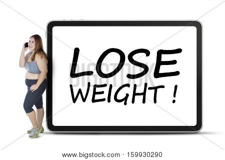Obese woman standing with lose weight text on billboard while speaking on smartphone isolated on white background