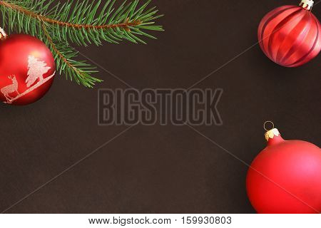 Dark background with Christmas fir branch red and wavy dull ball. Top view.