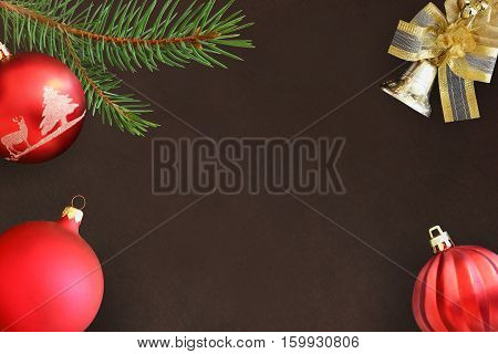 Christmas fir branch red wavy and dull ball and bell on a dark background