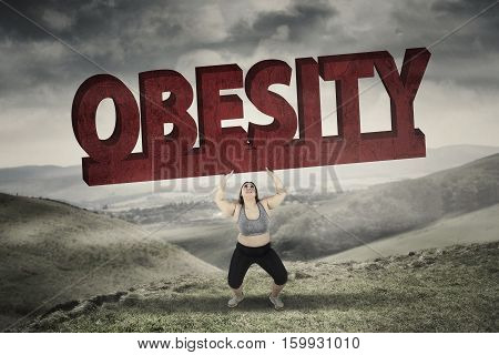 Picture of blonde hair woman lifting a big obesity word while standing in hills