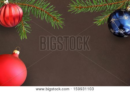 Dark background with Christmas fir branch red wavy dull and blue ball
