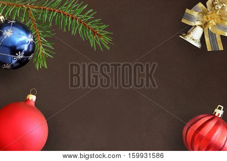 Christmas fir branch blue and red wavy dull balloon and decorative bell on dark background