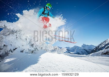 Freeride skier jumping from rock in freeze motion of snow powder.