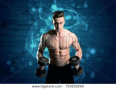 A sexy body builder lifting weight and showing his muscular, hot body in front of a blue urban brick wall with drawn light beams concept
