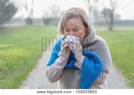 Senior woman in a warm woolly knitted winter scarf standing on a rural lane on a misty winter day