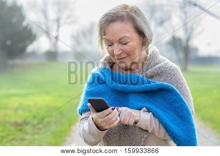 Attractive tech savvy elderly woman using a mobile phone texting a message to a friend or browsing for a number to call on a rural lane on a misty winter day
