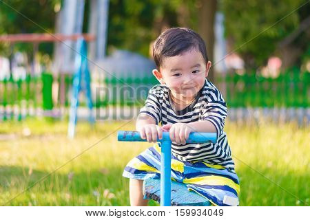 Asian Kid Riding Seesaw Board At The Playground
