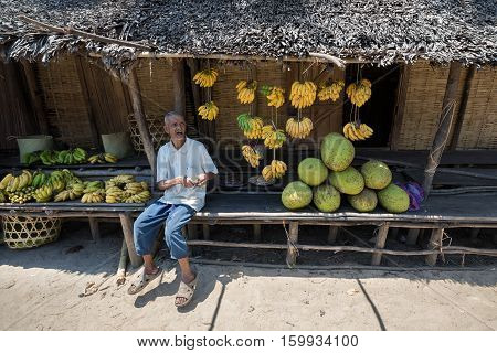 Malagasy Old Man Selling Fruit On The Market
