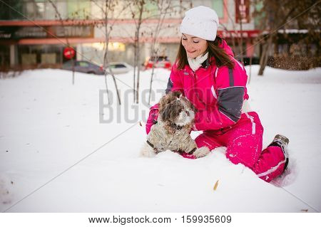 Walk In The Winter Outdoors With A Dog Breed Shih Tzu. A Woman In A Bright Red Warm Ski Clothing Wal
