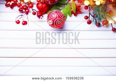 Christmas and New Year Decoration over white wood background. Border art design with holiday baubles. Beautiful Christmas tree closeup decorated with ball, holly berry, tinsel. Space for your text.